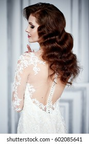 Close portrait of bride, caucasian, european girl brunette with makeup in white lace wedding dress with long head, with open back in studio with white background and stucco
