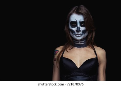 close up portrait of brown-haired woman with Halloween skull make up over black background.