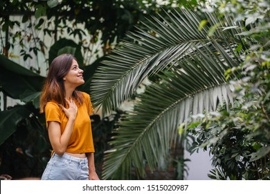 Close up portrait of brunette caucasian woman in yellow shirt and bkue denim shorts posing with palm leaf over green plant background in greenhouse. Real people model. Relax, summer, holiday concept.