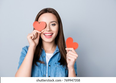 Close up portrait of brunette, charming, pretty girl, having two small red hearts in  hands, closing one eye with heart symbol,  while standing over grey background