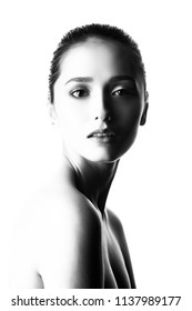 Close up portrait of a brunette girl with nude make-up and naked shoulders. Isolated on white background. Copy space. Advertising, fashion and commercial design. Black white photo.