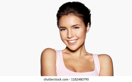 Close up portrait of  brunette girl in trendy t-shirt. Cute cheerful girl with fresh clean skin looking at camera with gladness and happiness. Isolated on grey