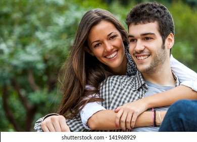 Close up portrait of brunette and her boyfriend in park.