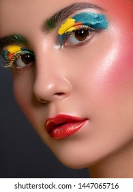 Close up portrait of Brunette woman with flawless clean skin. Creative colorful make up. Studio concept