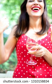 Close up portrait of brunette woman wearing polka dots dress having wine in a restaurant