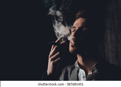 Close up portrait of brutal man in the smoke holding a cigar
