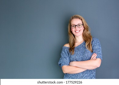 Close up portrait of a business woman standing against gray background with arms crossed