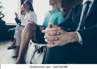 Close up portrait of businessman fingers crossed sitting surrounded by colleagues at presentation committee interview all dressed in formal wear jackets shirts