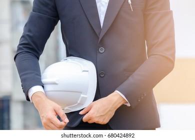 Close up portrait of businessman holding safety helmet