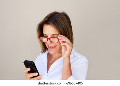 Close up portrait of businesswoman with glasses looking at cell phone