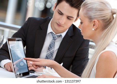 Close up portrait of businesswoman showing information on laptop to partner.