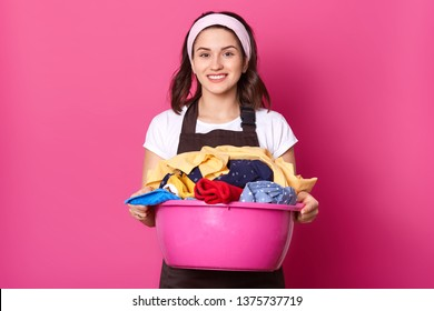 Close up portrait of busy young lady posing with laundry basin, looking directly at camera, being satisfied with quality of washing. Sincere housewife wearing brown apron, white t shirt and headband.