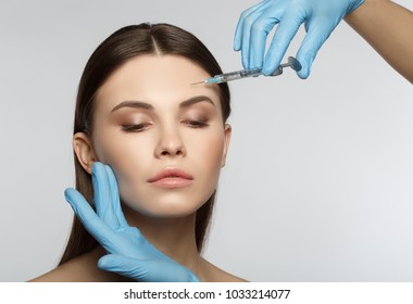 Close up portrait of calm female face. Young woman is getting collagen injection into her forehead. Isolated and copy space