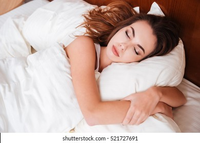 Close up portrait of a calm young pretty woman sleeping and hugging pillow in bed