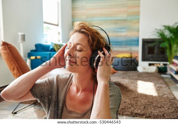 Close up portrait of carefree older woman listening to music at home