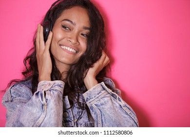 close up portrait of casual pretty woman enjoy listening a music on pink background