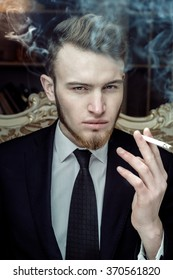 Close up portrait with casual young man sitting in vintage chair with a cigarette
