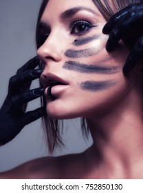Close up portrait of Caucasian female with hands painted smearing paint on her cheeks and lips dripping black paint