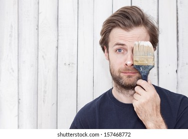 Close up portrait of caucasian forty years old man with a brush. Renovation - painting walls.  Image with free text space.