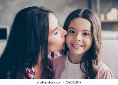 Close up portrait of charming cheerful smiling lovely mother kissing her adopted young cute beautiful girl