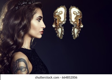 Close up portrait of charming lady with dark wavy silky hair and perfect make-up wearing jewel crown and looking in the face of Venetian mask hanging in the air. Backlight. Copy-space. Studio shot