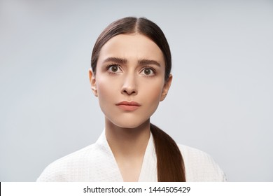 Close up portrait of charming lady with natural makeup looking away with serious concerned expression