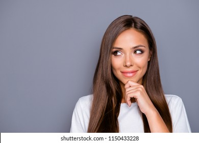 Close up portrait of charming and lovely young woman looks away keep her hand on the chin isolated on gray background with copy space for text
