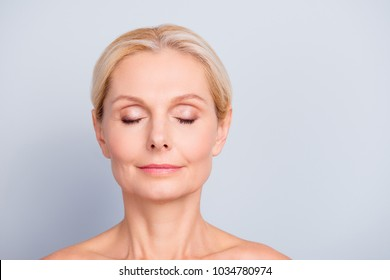 Close up portrait of charming, pretty, attractive woman with perfect skin after cream, balm, mask, lotion, isolated on grey background, having eyes closed, natural maqullage, make up