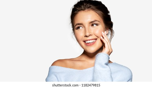 Close up portrait charming woman in stylish sweater posing at studio. Lovely cheerful girl touching her face and looking away with gladness. Isolated on grey