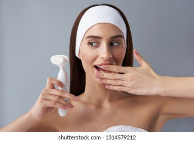 Close up portrait of charming young lady keeping hand near open mouth and staring at electric brush cleanser. Isolated on light blue background