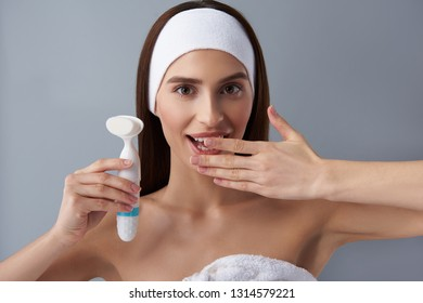 Close up portrait of charming young lady keeping hand near open mouth while demonstrating electric brush cleanser. Isolated on light blue background
