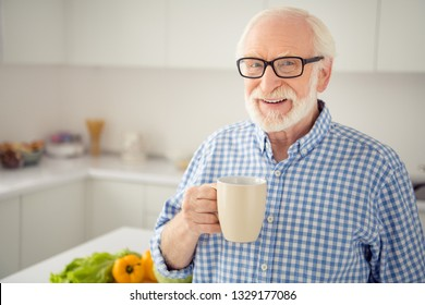 Close up portrait cheer grey haired he his him grandpa hot beverage hand arm look window ponder pensive imagination flight wear specs casual checkered plaid shirt jeans denim outfit light room