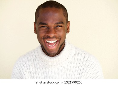 Close up portrait of cheerful african american man laughing against light background