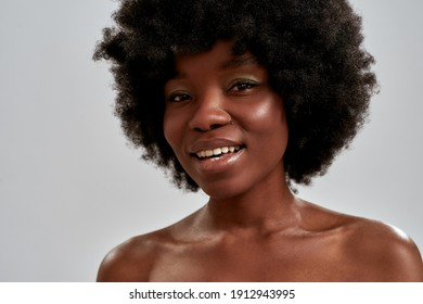 Close up portrait of cheerful african american young woman with afro hair and perfect smooth glowing skin smiling at camera while posing isolated over gray background. Skin care, diversity concept
