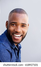 Close up portrait of cheerful african american man smiling against gray wall