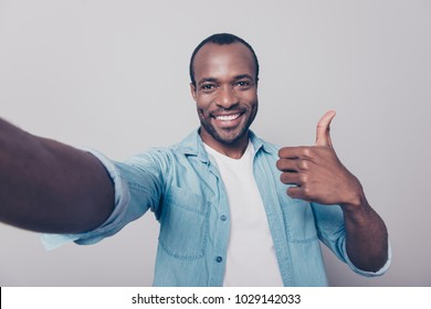 Close up portrait of cheerful excited satisfied glad confident guy wearing jeans casual shirt recommending to visit his place taking selfie demonstrating excellent symbol isolated on gray background