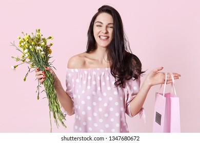 Close up portrait of cheerful female recieves present for birhday party, holds bag and flowers, looks happily, wears in dress, poses isolated over rosy background. Presents and celebration concept.
