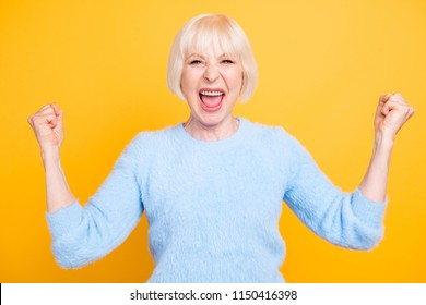 Close up portrait of  cheerful granny with toothy smile raised hands and showing successful celebrate goal isolated on vivid yellow background