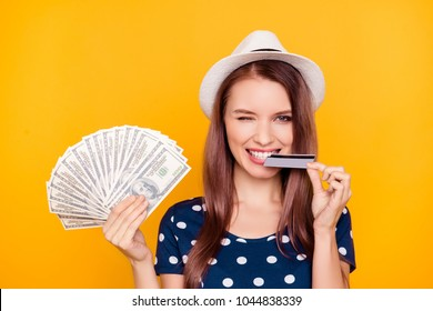 Close up portrait of cheerful, happy, pretty, charming,  girl in polka-dot t-shirt with hat on head, having money fan in hand, biting credit card with teeth, isolated on yellow background