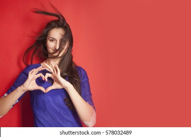 Close Up portrait cheerful happy young woman making heart sign with hands. Positive human emotion exp