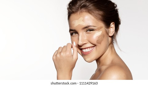 Close up portrait of cheerful lovable brunette applying tonal basis different shades for perfect natural maquillage. Beauty treatment concept. Isolated on grey background