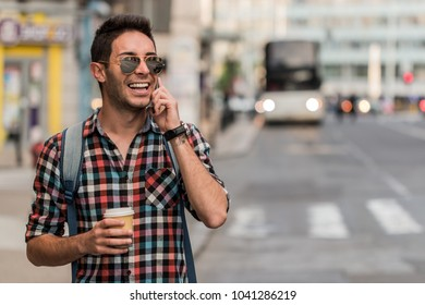 Close up portrait of cheerful mature man using mobilephone and laughing.