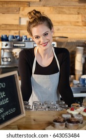 Close up portrait of cheerful owner standing by counter at cafe