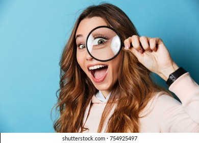 Close up portrait of a cheerful pretty girl looking through magnifying glass isolated over blue background