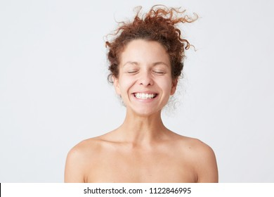 Close up portrait of cheerful pretty young woman with curly hair and healthy perfect skin keeps eyes closed shows her healthy teeth  isolated over white background Takes care of her appearance, stands