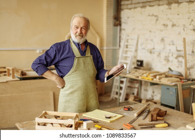 close up portrait of cheerful senior citizen chatting with clients. talking with customers. doing shopping online. internet is main helper for carpenter