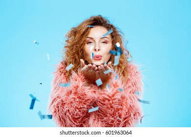 Close up portrait of cheerful smiling beautiful brunette curly girl in pink fur coat with confetti on foreground over blue background.