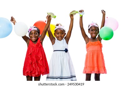 Close up portrait of cheerful threesome African youngsters holding colorful balloons.Isolated against white background.