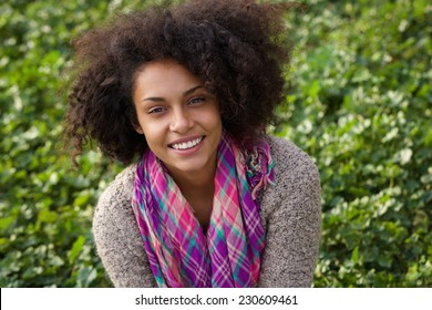 Close up portrait of a cheerful young african american woman smiling outdoors