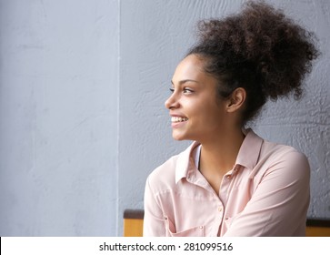 Close up portrait of a cheerful young african american woman smiling and looking away